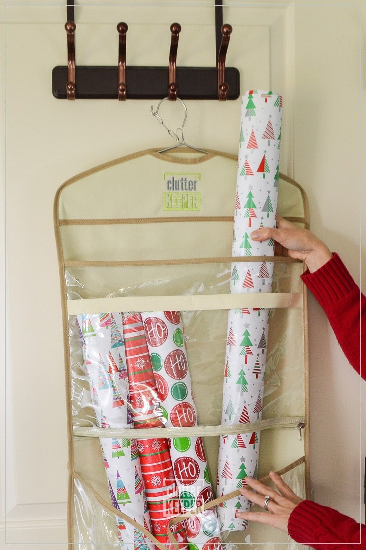 Sliding a roll of Christmas wrapping paper into a Clutter Keeper Deluxe Hanging Gift Bag Storage Organizer