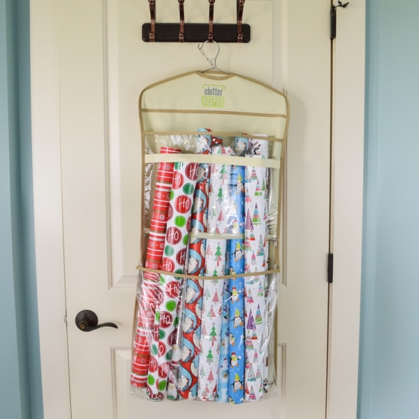 A Clutter Keeper® hanging organizer filled with Christmas wrapping paper rolls on the back of a door