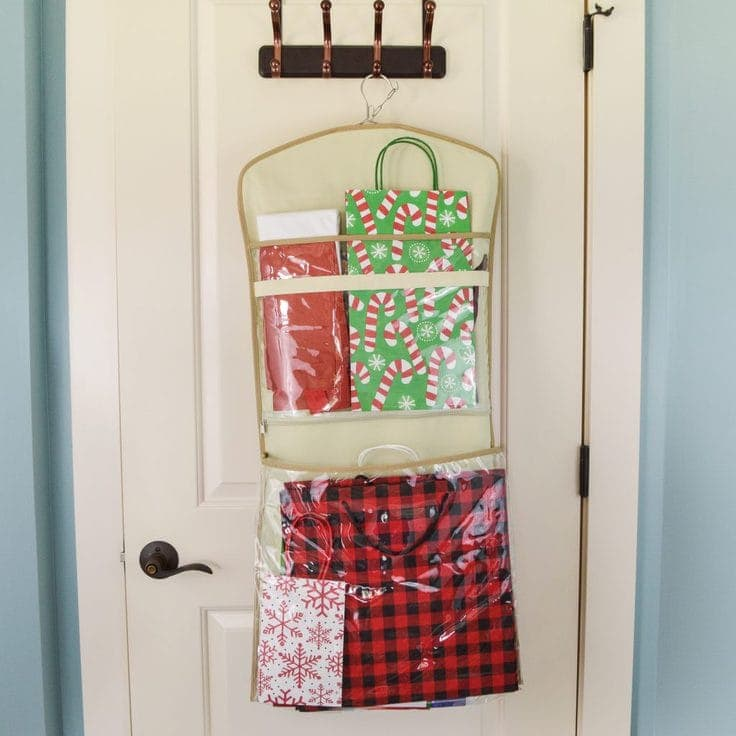 The back side of a hanging organizer showing two large pockets filled with Christmas gift bags and tissue paper