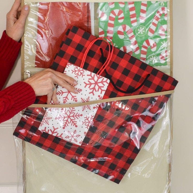 A close up of a woman's hands sliding gift bags into the pocket on a hanging gift wrap organizer