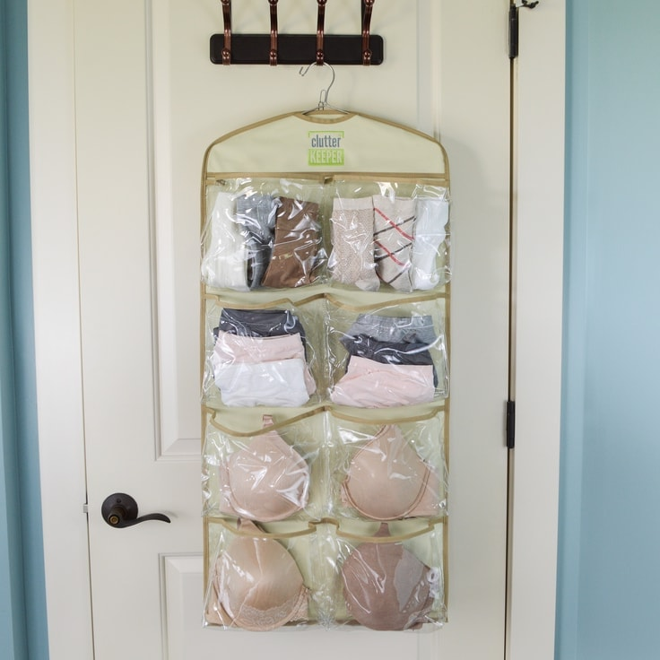 A Hanging Organizer filled with bras, underwear and socks on a hook on a closet door.