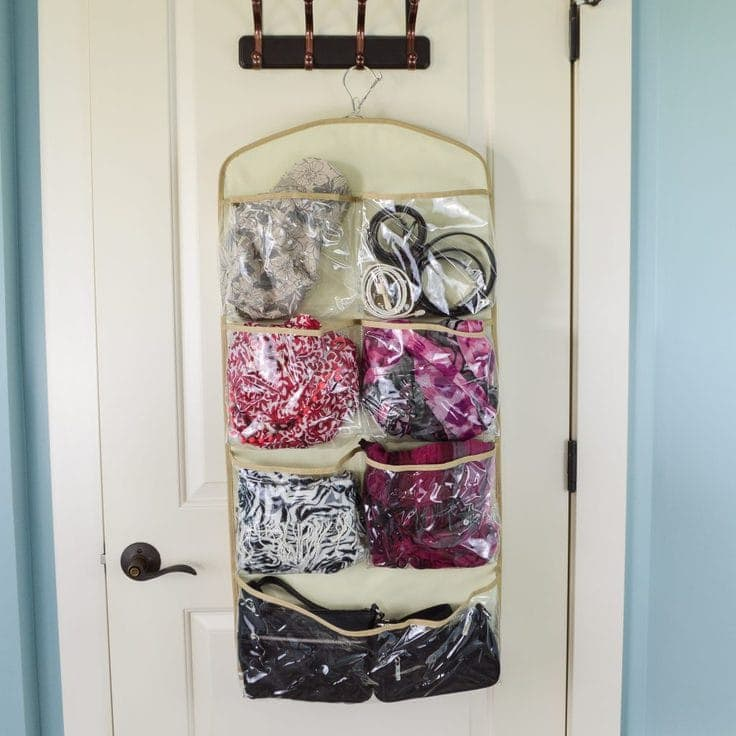 The back side of a hanging pocket organizer filled with scarves, purses, hats and other fashion accessories on the back of a closet door