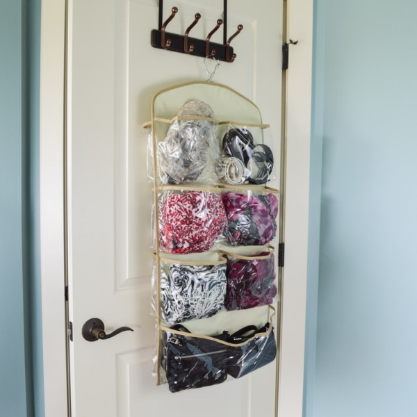 The back side of a Clutter Keeper 15 pocket hanging organizer filled with scarves, purses, hats and other fashion accessories on the back of a door