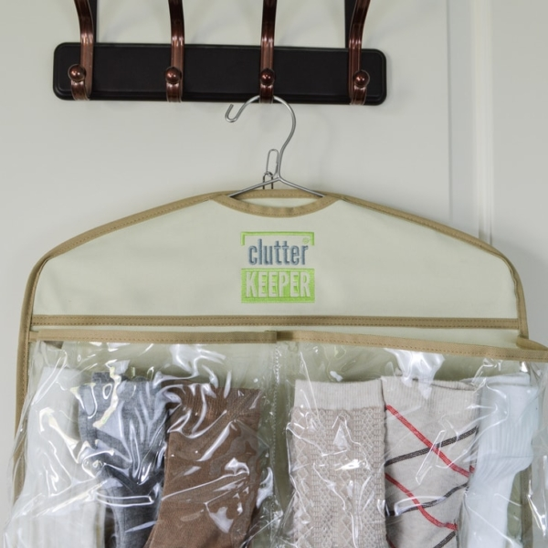 Close up of the top of a hanging organizer on a closet hook. Socks are shown in the pockets.