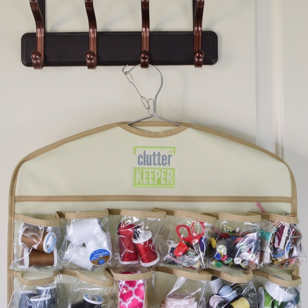 Close up of the top of a hanging organizer filled with craft supplies on a hook on the back of a door
