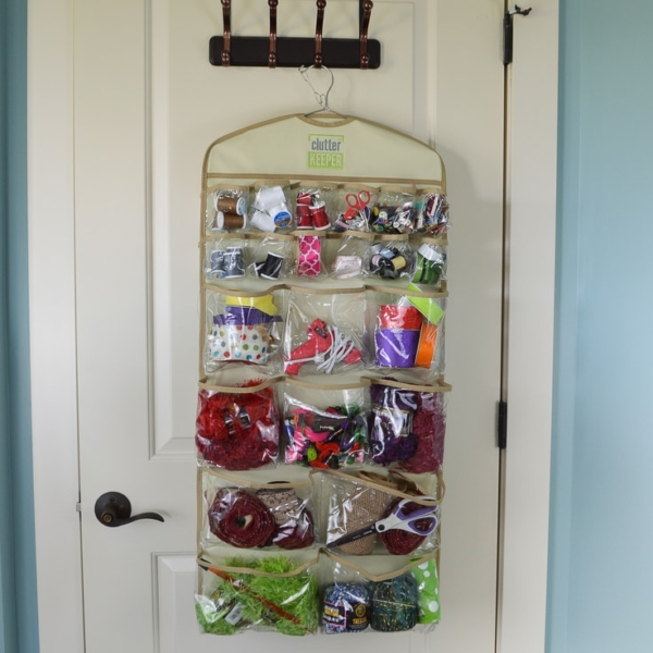Clutter Keeper® Deluxe 44 Pocket Hanging Storage Organizer filled with craft supplies hanging on the back of a closet door