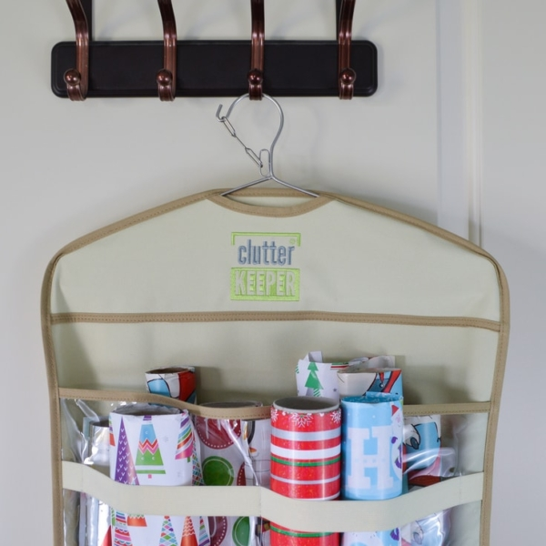 Close up of the top of a Clutter Keeper gift wrap organizer filled with rolls of Christmas wrapping paper hanging on a hook on the back of a closet door