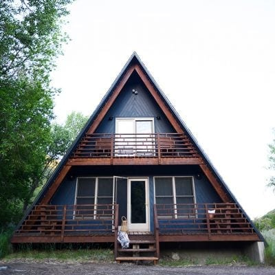 Front view of a tiny house with a triangular a-frame style roof
