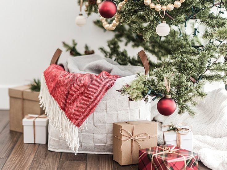 Close up of presents and baskets in front of a Christmas tree.