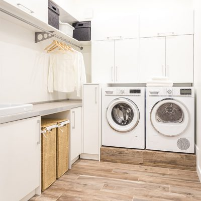 A laundry room with a washer and dryer, a sink, and a rod for hanging clothes to dry. The room shows a lot of laundry room cabinets and other ideas