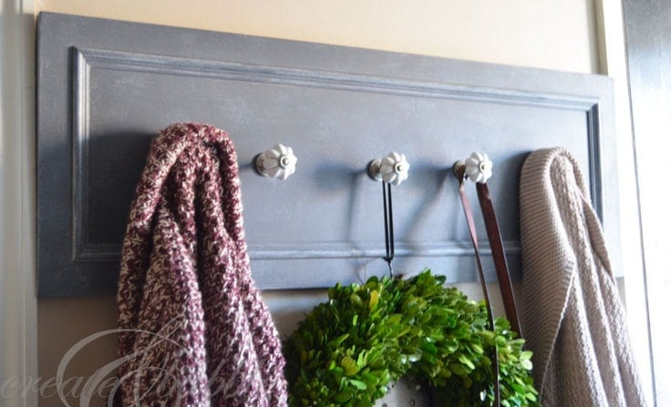 A coat rack made out of an old cabinet door.