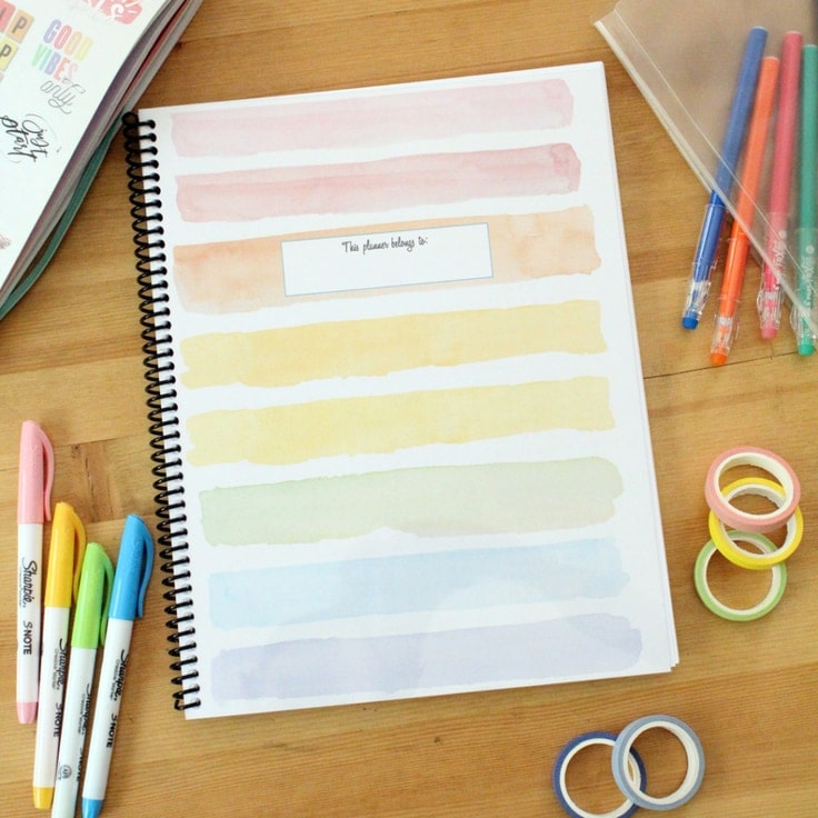 Keri Houchin rainbow striped spiral planner on a desk surrounded by pens and washi tape